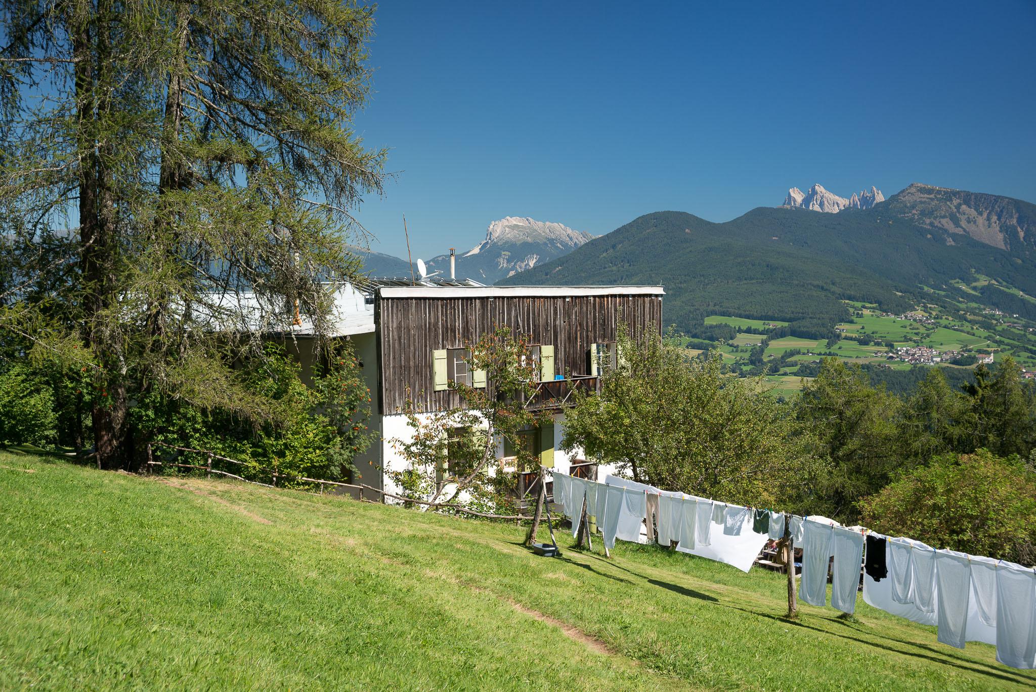 Blick von oberhalb auf die Pension Briol, rechts davon hängt die Wäsche auf langen Leinen und am Horizont sieht man die Dolomiten