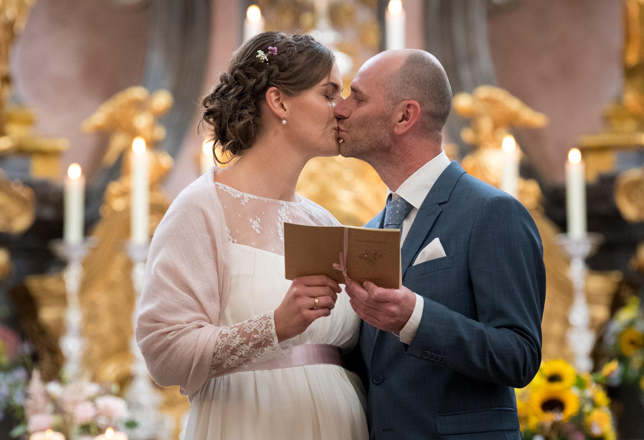 Brautpaar küsst sich in der Kirche