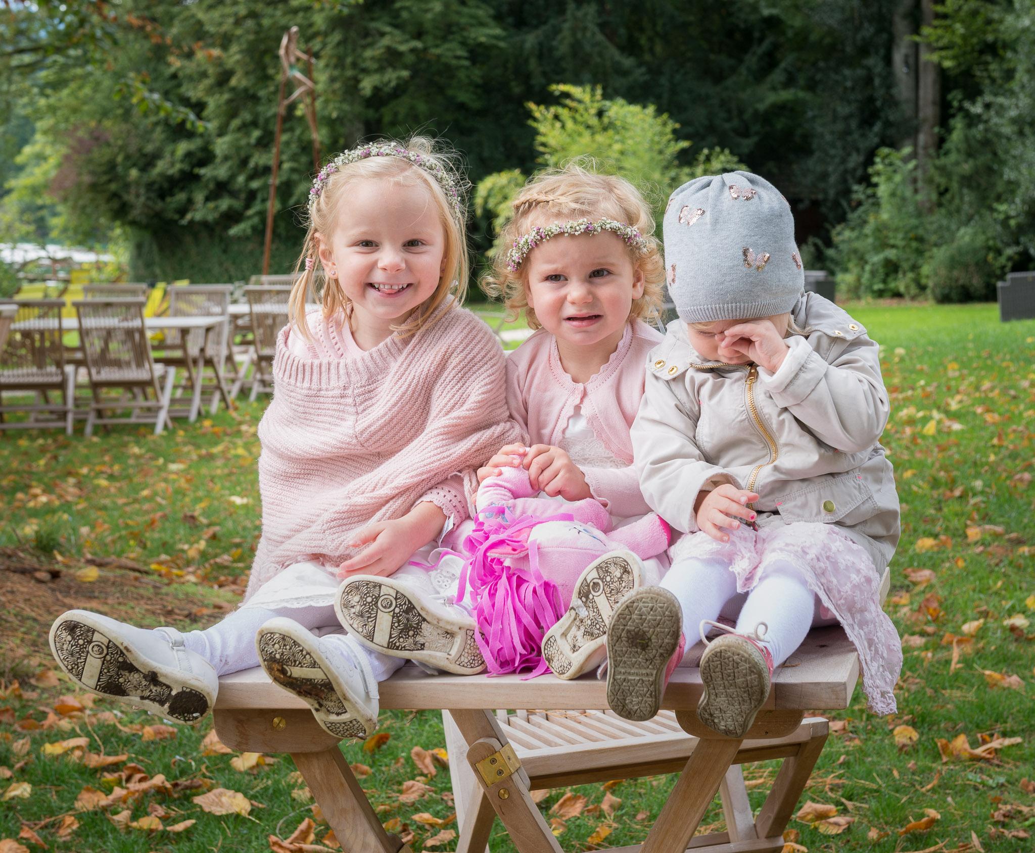 drei Mädchen sitzen im Garten auf einem Tisch