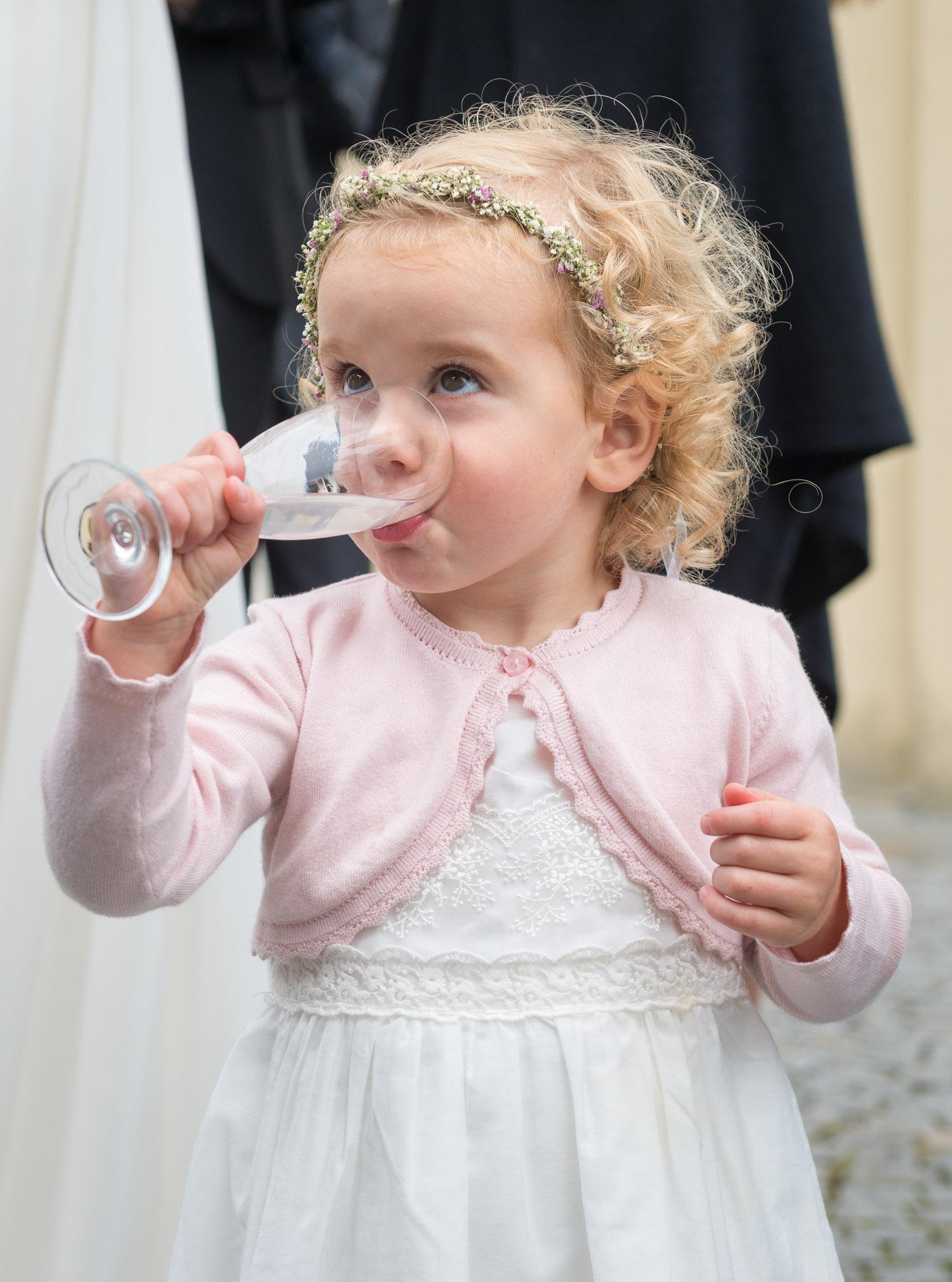 Mädel trinkt Wasser aus einem Sektglas